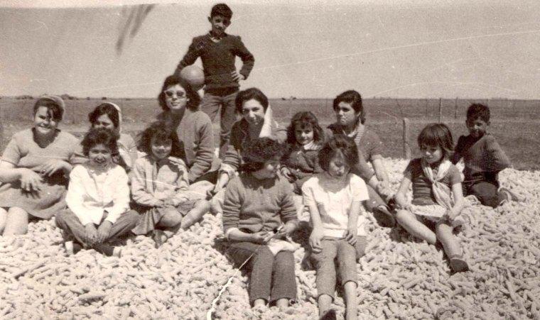 María Teresa Andruetto, la niña del pañuelo en el cuello, en un picnic el día del estudiante, con sus compañeros de piano, en un campo de la llanura cordobesa. Están sentados sobre una montaña de marlos (mazorca de maíz ya desgranado). La que se toca la cabeza es la maestra.