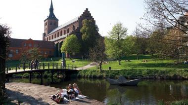 Paseo del río, estatua de barco de papel y catedral de Odense.