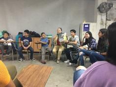 Nora Obregón leyendo con niños y jóvenes migrando.